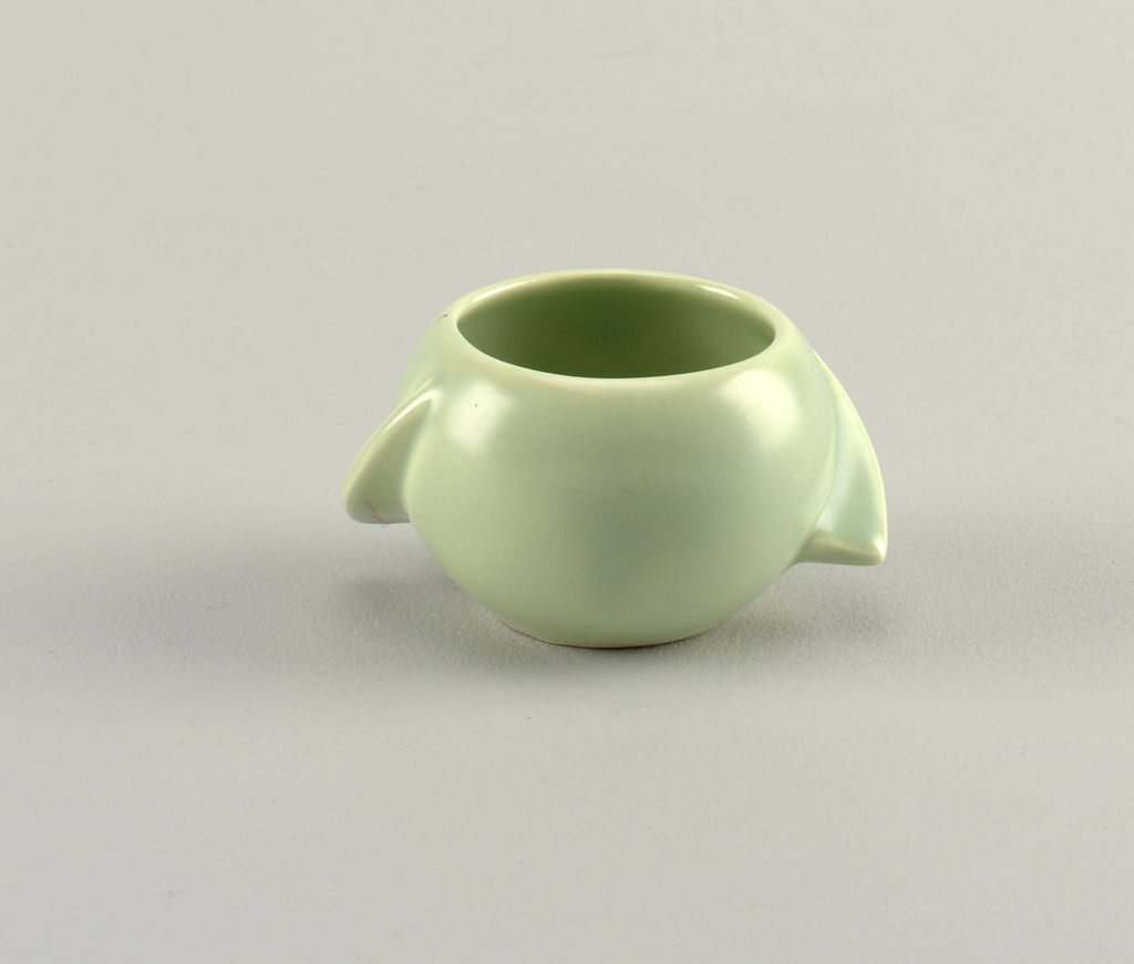Spherical bowl with symmetrically placed descending, widening, and curving tab handles.  Entire surface covered with light jade green glaze.