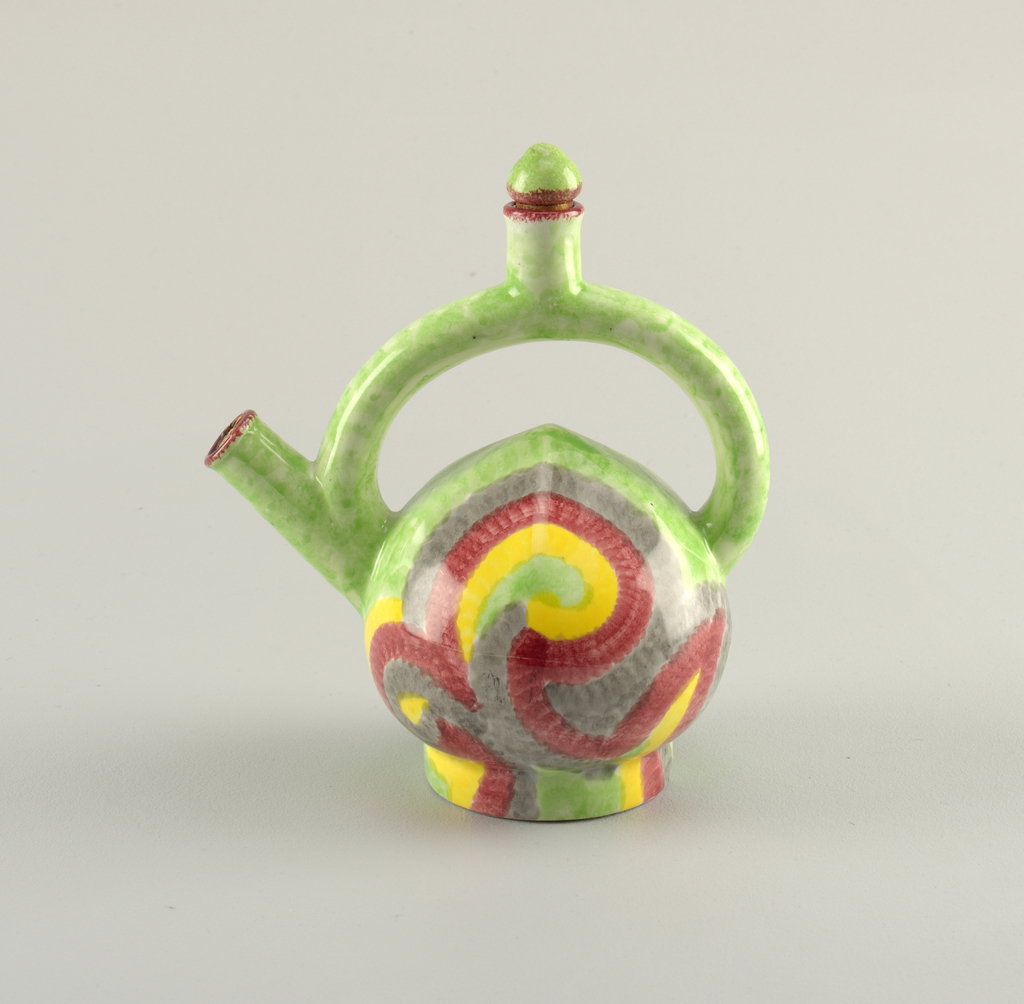Round body glazed in blue, red, yellow and green. The handle is curved and attaches  between the spout and the body and has a small cylinder opening in the center.