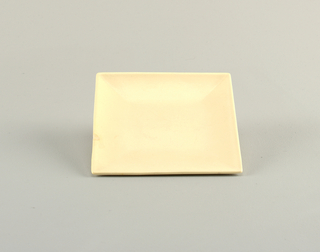 Square light peach with lined indentations reaching from edge to center.