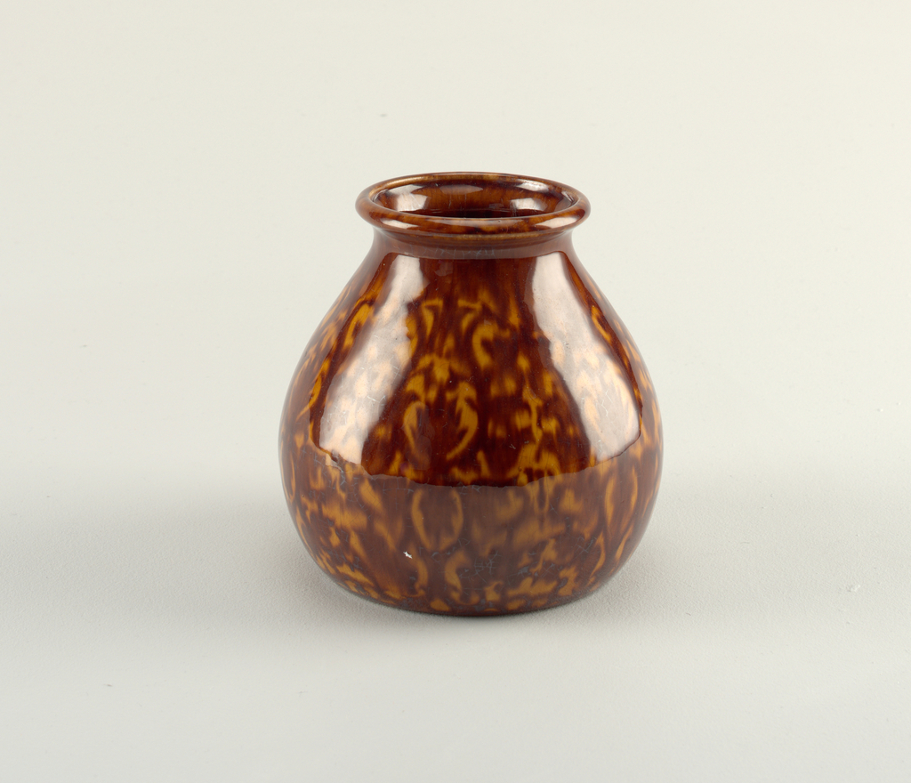 Round vase tapering toward the lip. Brown and orange pomegranate pattern glaze.