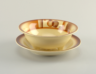 Circular bowl with out-curving lip sitting on three feet with six holes in the bottom.  Cream ground with a band of airbrushed decoration running along the interior of top edge consisting of overlapping swatches of rust and brown and two areas, across from each other, of overlapping rust and brown circles.   Circular underplate with slanted edge leading to a concave center with raised bottom rim.  Cream ground with airbrushed brown lining the edge.