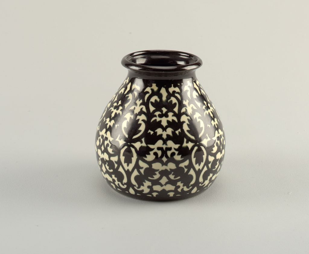 Round body tapering upward to a rounded lip. Black and white allover leaf pattern.