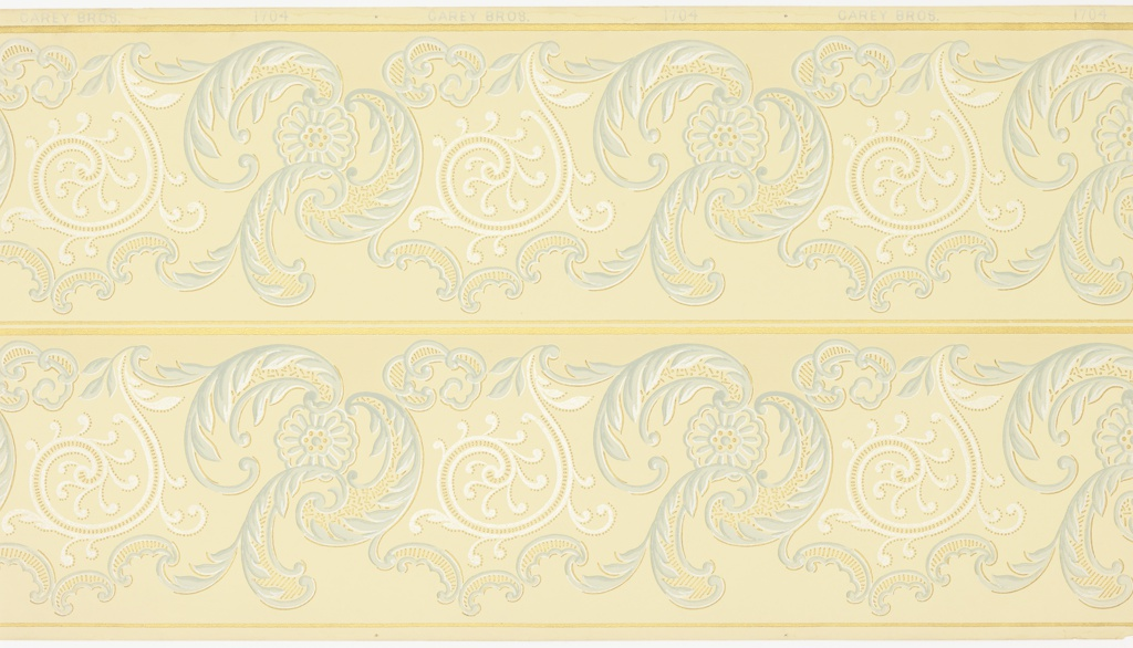 White scrolls and light gray-blue scrolling acanthus leaves with floral motifs alternate horizontally across the frieze. Between the lines of the scrolls and floral motifs are small dots and short lines that fill in the forms. Borders are printed two across the width. Printed in shades of gray, metallic gold and mica on a light yellow ground.