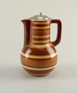 Jug with spherical lower body leading to a cylindrical shaped neck with an angular handle across from a blunt spout running the length of the neck.  Spout and handle painted brown and the body is striped with brown, burnt, orange, and cream.  Dome-shaped round metal cover with a ball finial.