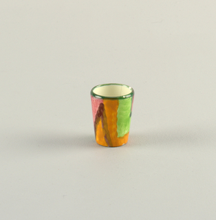 Small cylindrical cup.  Green-lined top edge with surface horizontal stripes of zig zags in brown, orange, green, and rose.