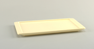 Rectangular light peach with handles extended from tray in striations.