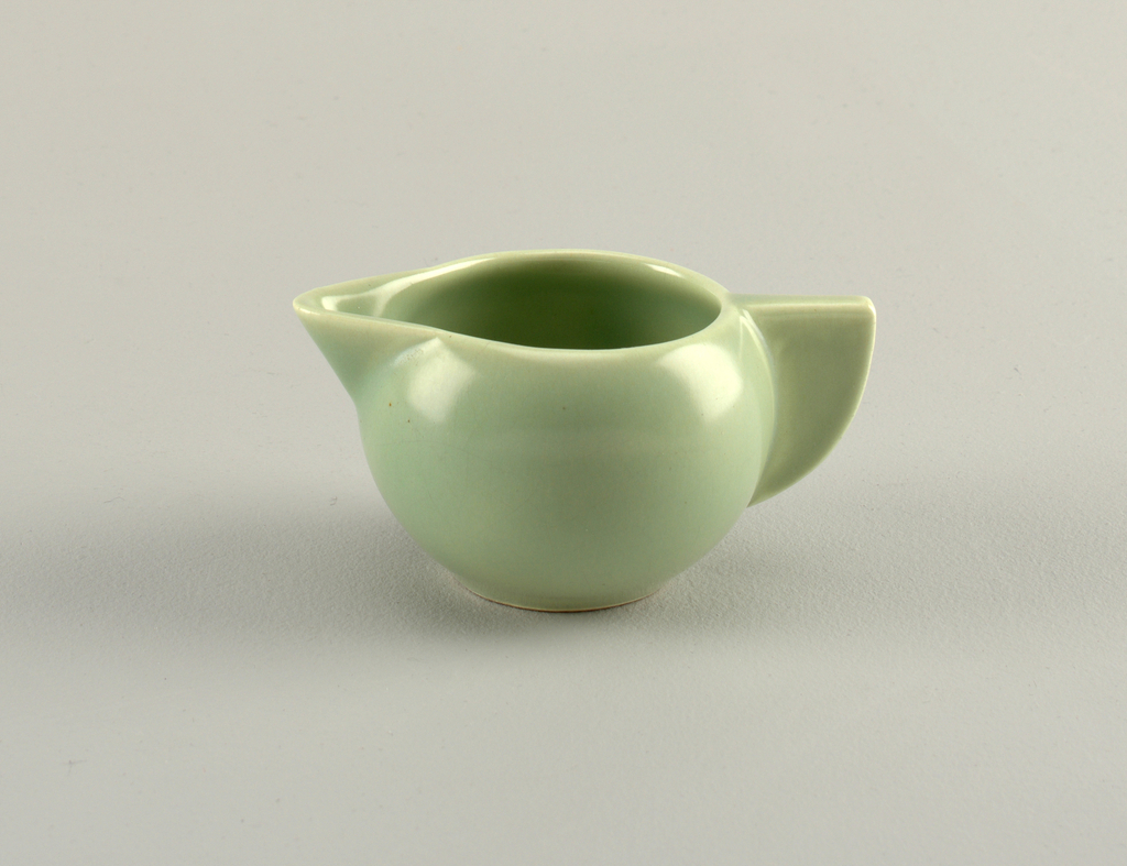 Spherical pitcher with a triangular spout sitting across from a solid handle shaped like a quarter of a circle.  Entire surface glazed with a speckled light jade green ground.