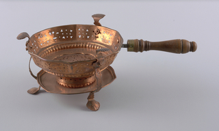 Dish is a decagon in plan, rounded with gadrooning at bottom. Pierced throughout. Three shell-shaped prongs connecting to shell-shaped feet. Turned wood handle.