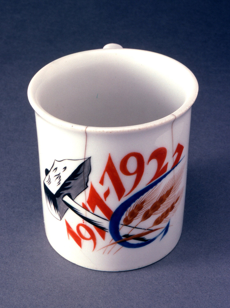 "Cylindrical, with straight sides flaring slightly at top, loop handle; painted with ""1917-1927"" in orange, with a large hammer, sickle, and three wheat stalks"