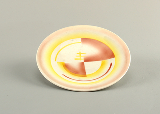Circular concave plate with raised bottom rim.  White background with airbrushed pink lining the edge.  Interior circle of airbrushed yellow containing a design of semi-circular lines in yellow and rose, four crossed lines in yellow, and two solid quarer-circles in rose.