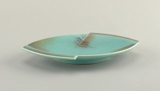 Oval dish with pointed ends, raised bottom rim, and two curving protrusions about half the length of the dish on opposite sides at the ends.  Turquoise ground with airbrushed brown that lines the protrusions and the ends.  On the edge near the center of each side lies a pattern of wavy and straight crossed brown lines, a rust-colored swatch, and blue dots.