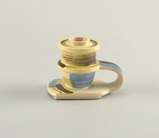 Strap handle connecting central ring and base. Additional rim forming drip pan at top. Creamy ground glaze with abstract design in blue, brown and yellow.