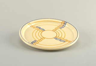 Circular concave tray with beveled upper rim.  Cream ground divided into quadrants by wavy blue and orange lines coming off of a central orange circle.  Also, other orange partial circles radiating out from the center.