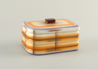 Box and lid in white, purple, and brown. Box of horizontal ribs with lid that has a square brown finial.