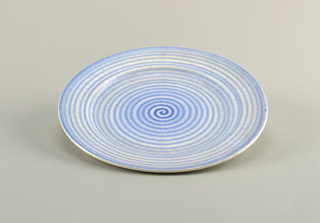Circular plate with a concave center and raised bottom rim.  Cream ground with a fuzzy blue swirl covering the entire surface creating a pattern of concentric circles.