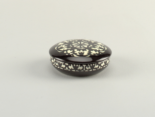 Circular box and slightly domed lid, the arabesque decoration in underglaze black on white; interior in underglaze black.