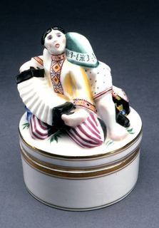 Cylindrical in shape, straight sides; the figures of a male accordion player and a woman seated sculpted on top of lid; painted in polychrome enamels, gilt bands around upper and lower edges of base and lid.