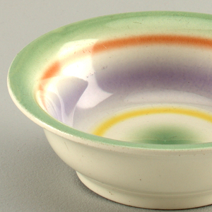 Round dish with green rim followed by a red stripe, a wider blue stripe, a thinner yellow stripe and finally a green center.