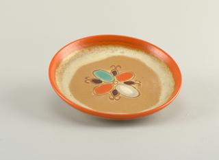 Circular dish with a raised bottom rim.  From outside edge, glaze is done in uneven circles of orange, cream, and tan.  Centered design with brown outline of a stylized flower with central circle surrounded by four ovals of white, orange, and turquoise alternating with four pineapple-like shapes with dark brown centers.