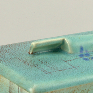 Rectangular turquoise box and lid speckled with brown and Asian-inspired crosshatching motif with blue dots. Lid hangs over rim of box, with two curved rectangular pieces that act as finials.