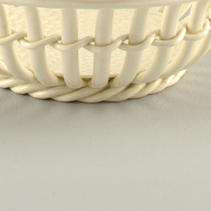 Cream-colored circular openwork form with flaring mouth and circular floor with basket-weave surface.