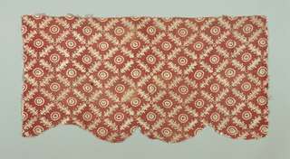 Part of a small valance in coarse cotton printed in red with a pattern in white of a trellis of leaves with a rosette center.