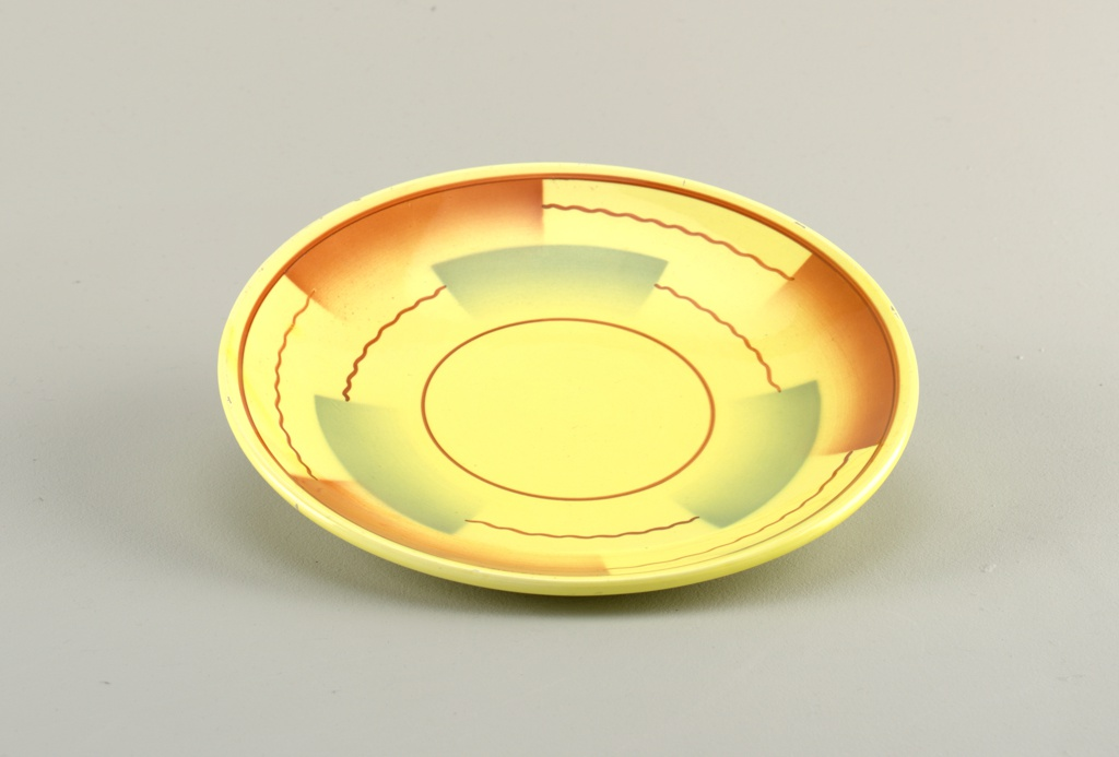 Shallow circular dish with up-curved rim, circular foot ring; decoration of yellow ground with straight and wavy brown lines forming concentric circles broken by semi-rectangular airbrushed swatches of brown and green.