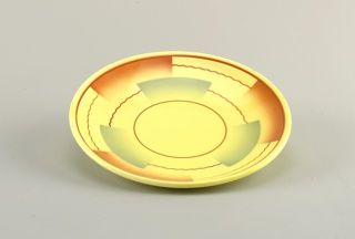Circular shallow dish with raised bottom rim.  Yellow background with straight and wavy brown lines forming concentric circles broken up by semi-rectangular airbrushed swatches of brown and blue.