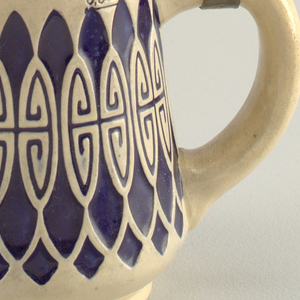 Tapering cream-colored tankard with pressed pattern glazed blue. Hinged lid with design. Half liter mark.