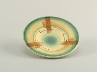 Circular concave form with a raised bottom rim.  Cream ground with concentric airbrushed circles from the edge of green, burnt orange, green, and cream with curving and bending brown lines, and a green center.  Overall composition is broken into thirds by wide airbrushed brown bands.