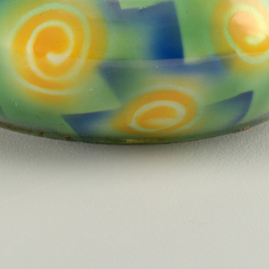 Circular form, widest at middle, with four equally spaced triangular tabs near the top rim.  Cream interior and green exterior background with a thin line of black at the top edge.  Pattern, on exterior, consists of orange swirls and blue step-like forms.