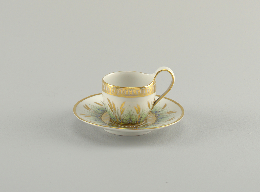 Curved cup with high looped strap handle. Saucer is slightly curved. Overglaze decoration on cup showing flowers, wheat and green grass. Gold edges and bands.