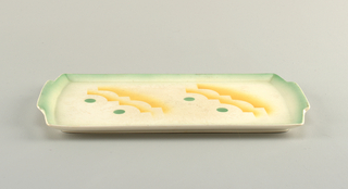 Rectangular concave plate with protruding tabs at each of the narrower ends.  Cream background with mint green lining the entire outer edge of the plate.  Central airbrushed design of two identical sets consisting of two green circles bordered by yellow outlines in the shape of conjoined semicircles and ninety degree angles.