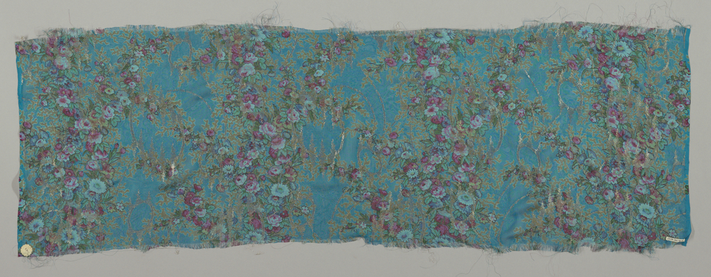 Sample of sheer teal-colored silk with a multicolored print of four vertical columns formed by solidly massed small-scale flowers. Over this, a design of scrolling lines, circles and irregular lozenges brocaded in metallic gold thread. Both selvedges present.