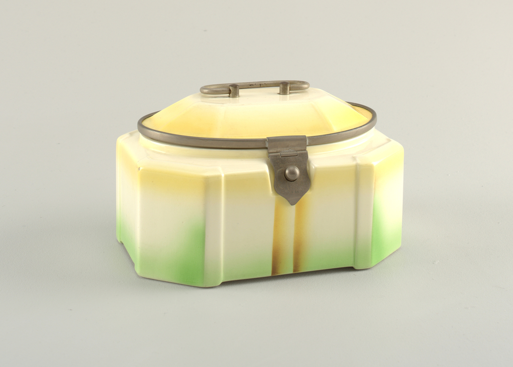 Faceted rectangular box with domed lid. Metal hinge, clasp and handle. Light yellow and blue gradiated glaze.