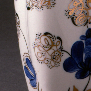 Four-sided, swelling at corner edges, tapering at base and towards short flared neck; painted with blue and gilded stylized flowers and foliage.