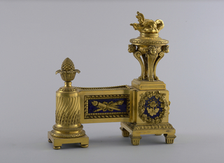 Flaming tripod urn on a plinth with blue enamel backed applique; joined by a blue enameled flambeaux panel of sertentine fluted columnar plinth with cone finial.