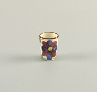 Small cylindrical cup.  Cream ground with a line of burgundy on the top rim and on exterior surface two burgundy and blue flowers with yellow centers surrounded by green leaves.