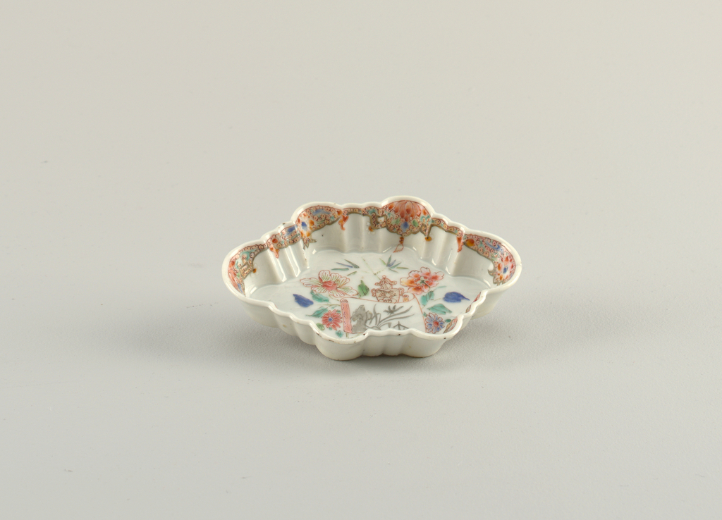 Scalloped plate, bordered with floral pattern along with tassels. In well, plate decorated with an opened scroll before and urn and flowers.