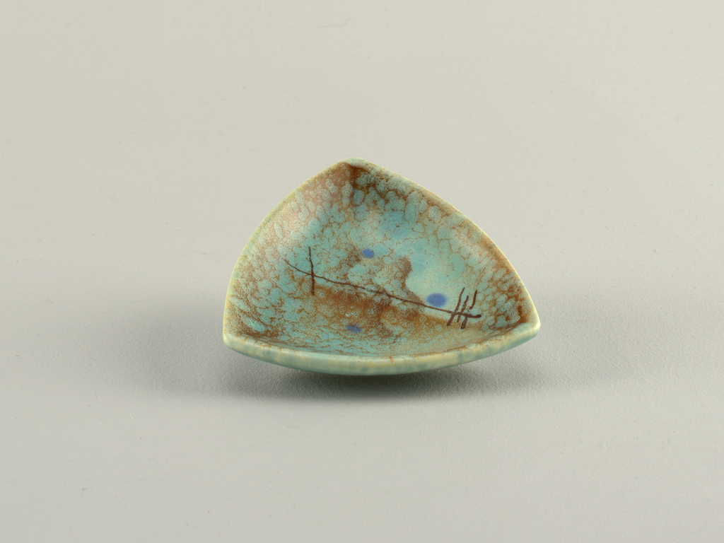 Triangular dish with curved sides and raised bottom rim.  Turquoise ground with overlying speckles of brown.  Center airbrushed design of three wavy brown lines, five crossing brown straight lines, a rust-colored swatch, and three blue dots.