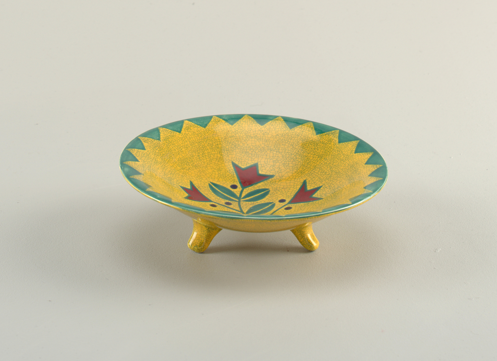 Circular dish on three feet. Yellow glaze with crazing. Stylized tulips red and green.
