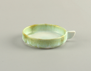 Low round cup with a quadrant handle. Light green and yellow glaze dripping over a white ground.