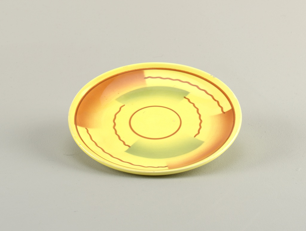 Circular plate with raised bottom rim.  Yellow background with straight and wavy brown lines forming concentric circles broken up by semi-rectangular swatches of airbrushed blue and brown.