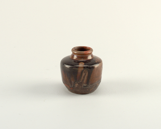 Ovoid form with flat shoulders.  Thick brown and black glaze dripped and terminating irregularly.  Glaze has irredescent flecks on edges and around shoulders.  Dark brown glaze in interior.  Strong turning marks.