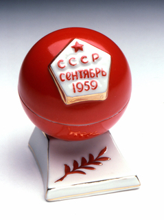 """In the form of a red orb on a low plinth; on the orb a pentagonal plaque with red star and inscription (in Russian): """"USSR / September / 1959."""""""