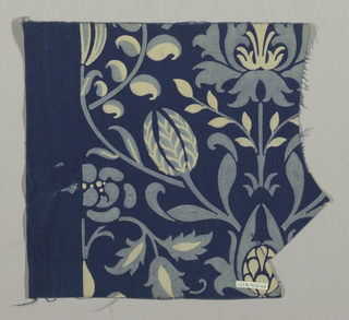 Symmetrical stylized floral design in light blue and white on a dark blue ground. Wide dark blue selvedge with selvedge cord of bunched threads.