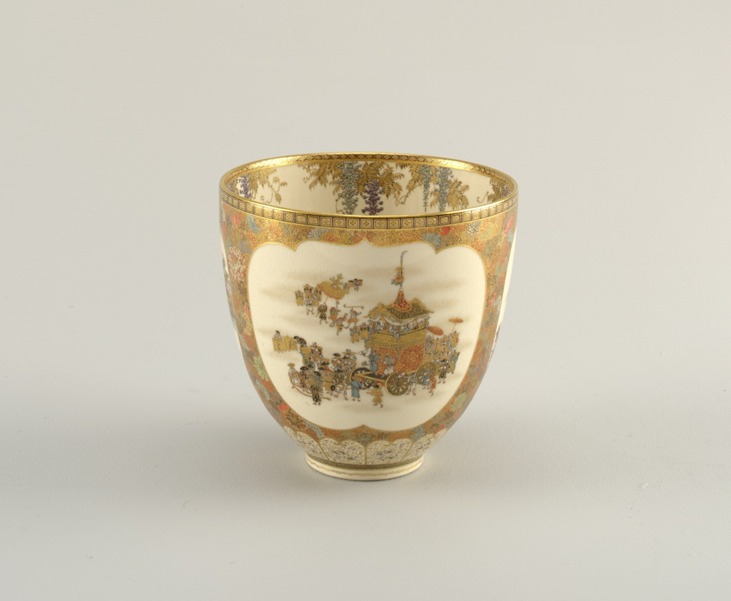 Deep round bowl on slightly undercut foot.  On ground of cream-colored small-crackle glaze, Satsuma style decoration: all over patterns of closely-packed multi-colored chrysanthemums, predominant colors, gold and red.  Three reserves with scenes: 1) procession with large-wheeled, roofed float, 2) lillies and butterflies, 3) sail boat off rocky coast.  Interior: over cream ground, wisteria branches drip from rim.