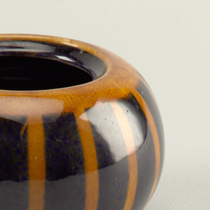 Round bowl with wide circular opening at top. Missing lid. Orange and brown striped decoration.