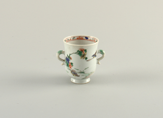 Famille verte footed beaker with two dolphin-form handles. Painted florals with duck; painted band of ornament inside the rim.