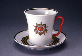 """Cup (a) cylindrical, flaring towards top, red loop handle; insignia painted on one side inscribed (in Russian) """"The Patriotic War."""" The saucer (b) painted with folded striped ribbon circling border."""